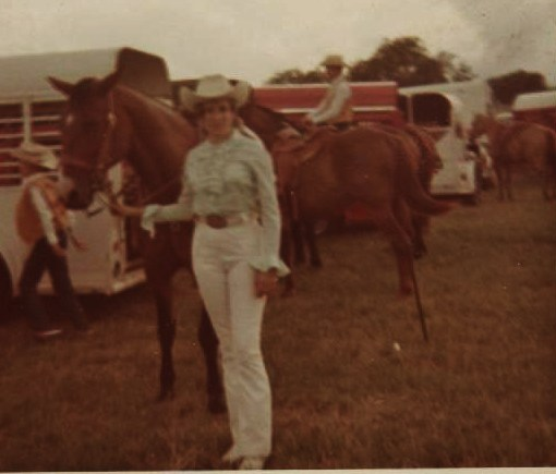 PHOTO OF MARSHA STANDING  BESIDE HORSE, DRESSED IN WHITE